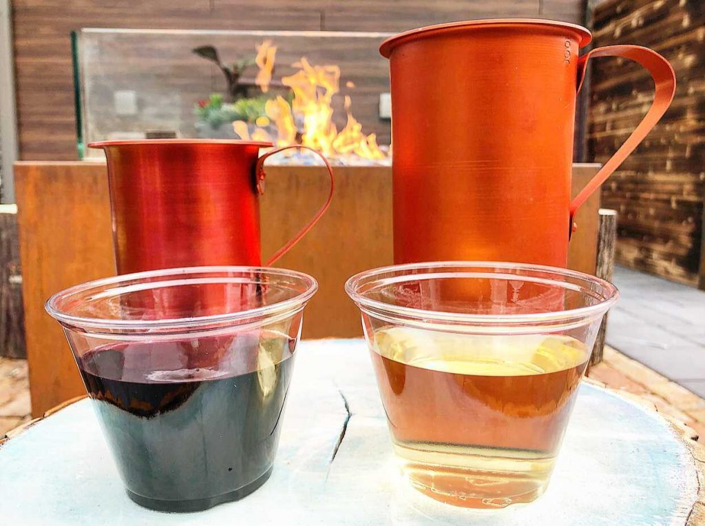 two plastic cups of wine, one red and one white