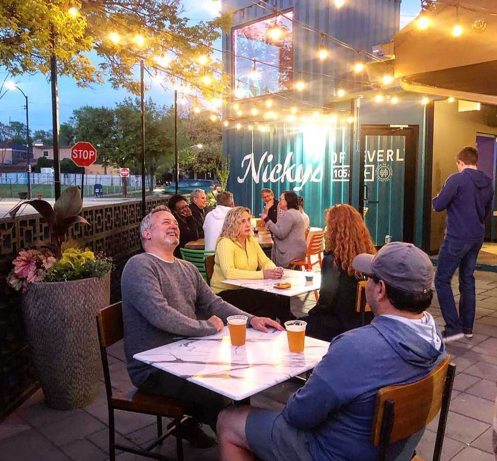 people sitting at tables outdoors at Nicky's of Beverly, laughing, talking, and drinking beer and wine